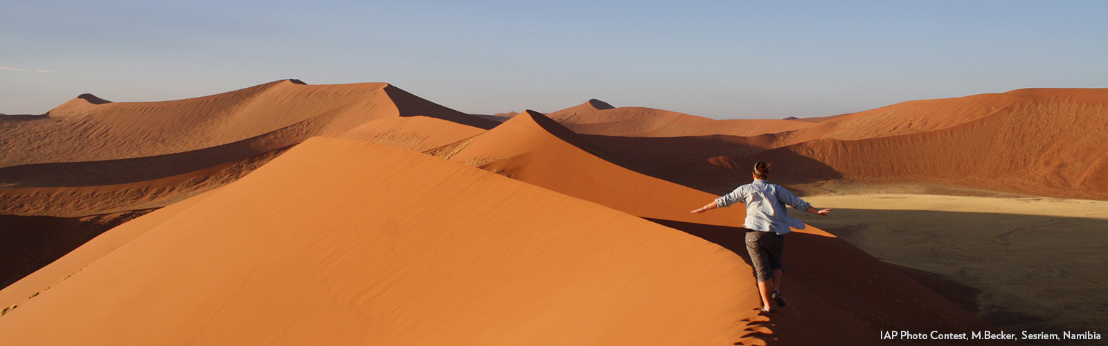 Photo of student walking along sand dun in Namibia